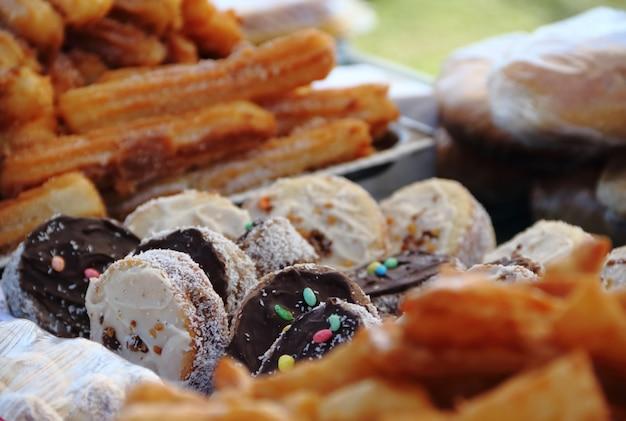 Alfajoresのフライドケーキとチュロの街頭フェアでの販売 Premium写真