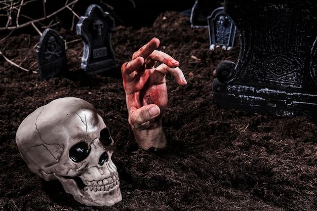 Viva mano con sangue che sporge dalla tomba Foto Gratuite