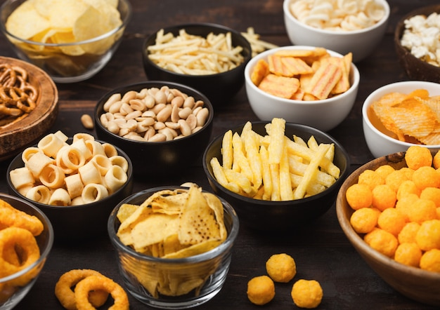 All classic potato snacks with peanuts, popcorn and onion rings and salted pretzels in bowl plates on wood. twirls with sticks and potato chips and crisps with nachos and cheese balls. Premium Photo