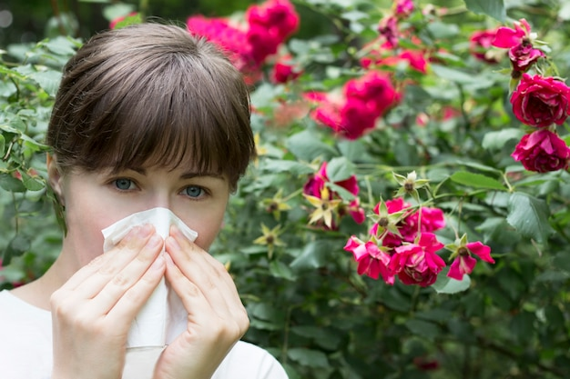 Allergy to flowering. a young girl sneezes. irritation Premium Photo