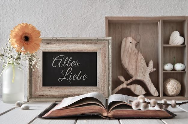 春の背景に開いた本、季節の装飾、ドイツ語でテキストalles liebe Premium写真
