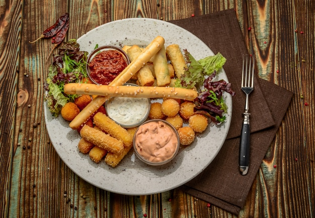 Allsorts of fried snacks with two different sauces on black Premium Photo