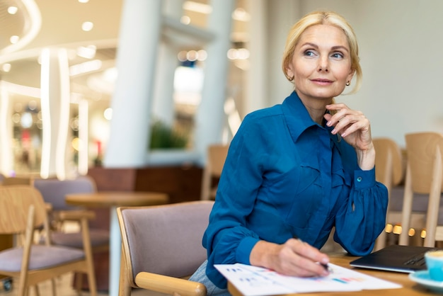 Очаровательная пожилая деловая женщина, имеющая дело с бумагой во время работы на ноутбуке Бесплатные Фотографии
