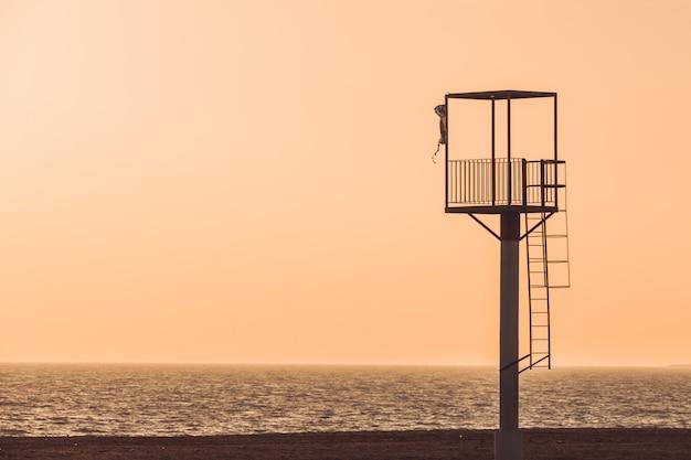 Almerimar beach lifeguard tower at sunset. Premium Photo