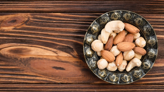 Almond; cashew nut and hazelnuts in antique metallic bowl on wooden desk Free Photo