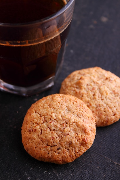 Almond cookies on a black background with a cup of coffee Premium Photo