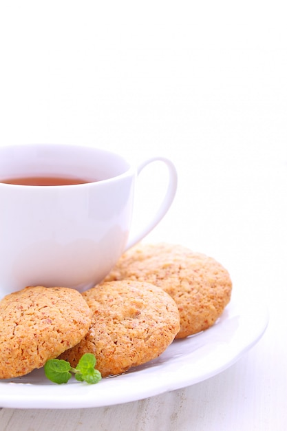 Almond cookies in a white plate with a cup of tea Premium Photo