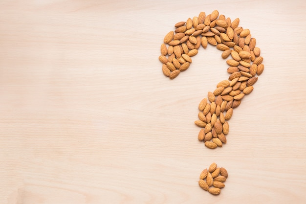 Almond in the shape of question mark on light wooden background. nuts on the table Premium Photo