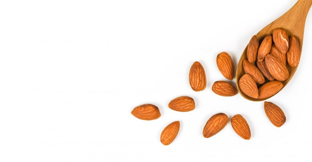 Almonds nuts on wooden spoon / close up almond isolated on white background Premium Photo