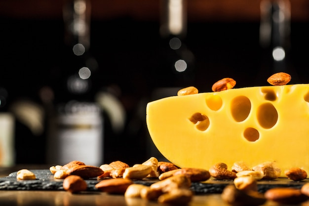 Almonds and peanuts lie on piece of swiss cheese Free Photo