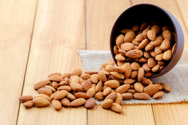 Almonds pour from wood cup Premium Photo