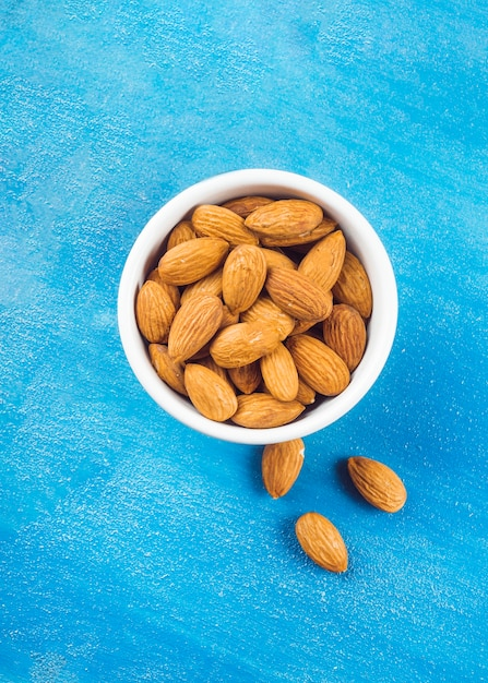 Almonds in white bowl on blue textured backdrop Free Photo