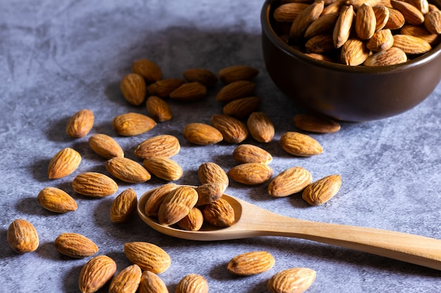 Almonds with wooden bowl and spoon on the dark table. Premium Photo