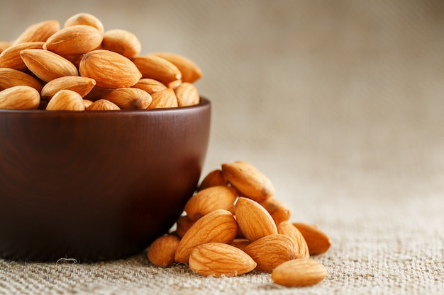 Almonds in a wooden cup on a burlap cloth . Premium Photo