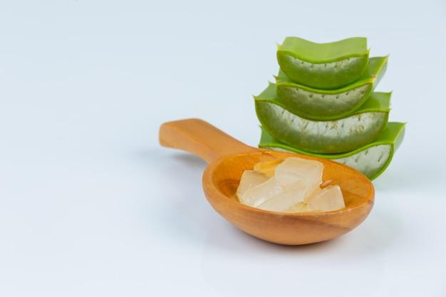 Foglie fresche di vera dell'aloe con le fette e gel sul cucchiaio di legno. l'aloe vera è l'uso naturale di erbe per la bellezza. Foto Gratuite