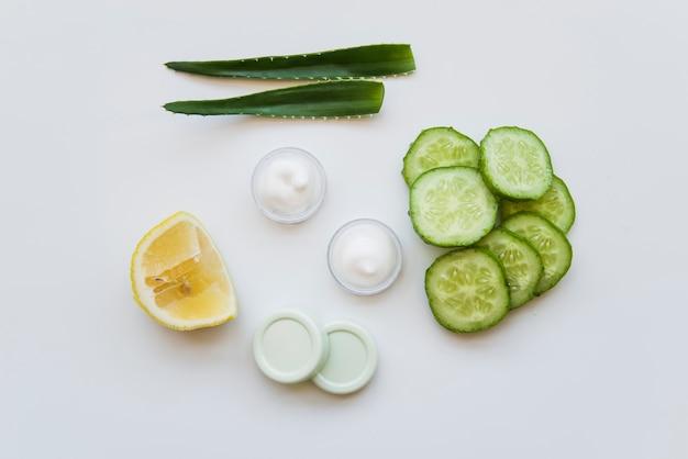 Aloe vera leaves; moisturizer cream; lemon and cucumber slices on white backdrop Free Photo