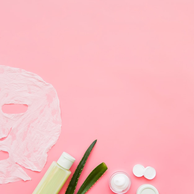 Aloe vera skin cream; lotion and paper sheet face mask on pink backdrop Free Photo