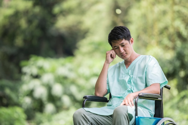Alone young disabled man in wheelchair at the garden Free Photo
