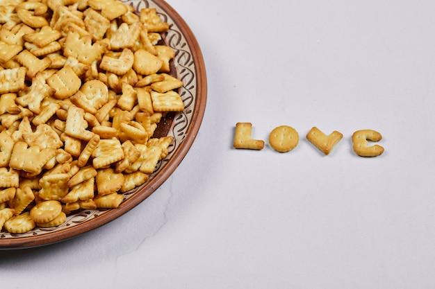Крекеры с алфавитом на керамической тарелке и слово «любовь», написанное крекерами. Бесплатные Фотографии