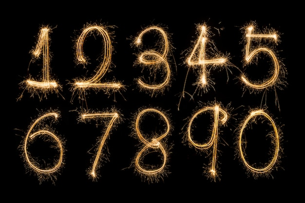 Alphabet and numbers sparklers on black background Premium Photo