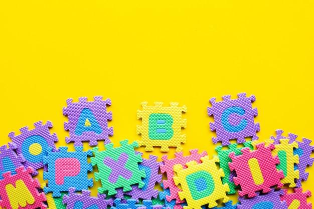 Alphabet puzzle on yellow. Premium Photo