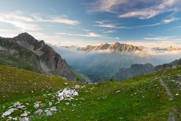 Alpine meadow and pasture set amid high altitude mountain range at sunsets Premium Photo
