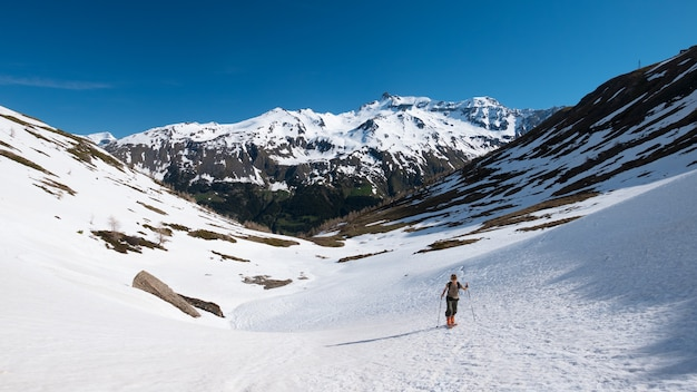 Alpinist hiking ski touring on snowy slope towards the mountain summit. concept of conquering adversities and reaching the goal. Premium Photo