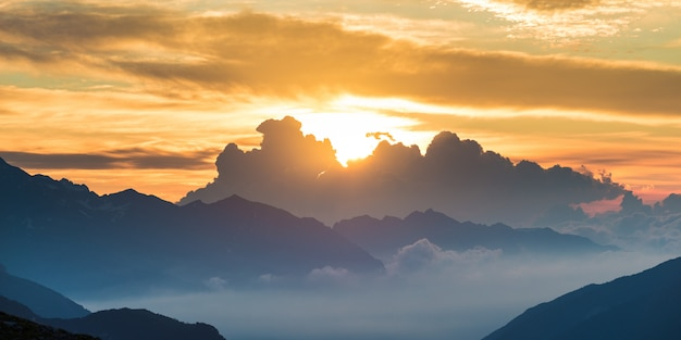 The alps at sunrise. colorful sky majestic mountain peaks, fog mist valleys. Premium Photo