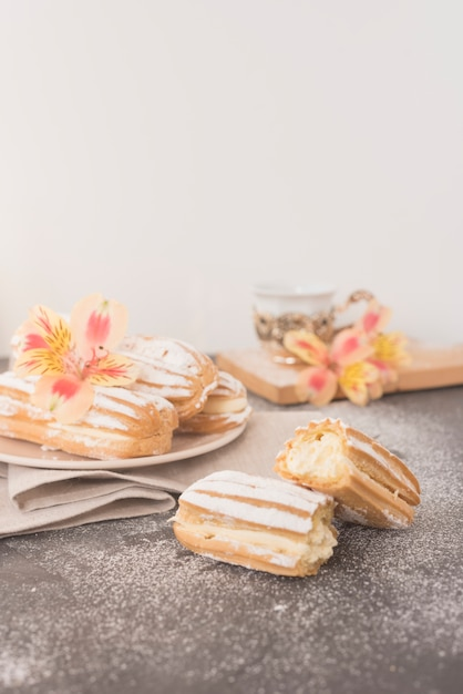 Alstroemeria flower on homemade eclairs against white backdrop Free Photo