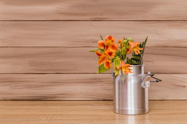 Alstromeria flowers and ferns in milk jug Free Photo