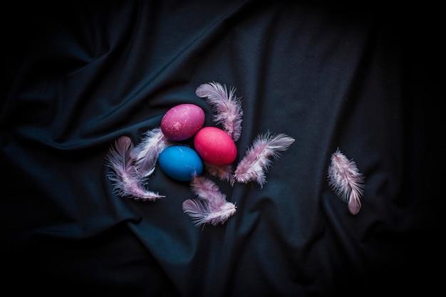 黒の上に年配の女性の卵、羽、手で暗いスタイルの代替イースター構成 Premium写真