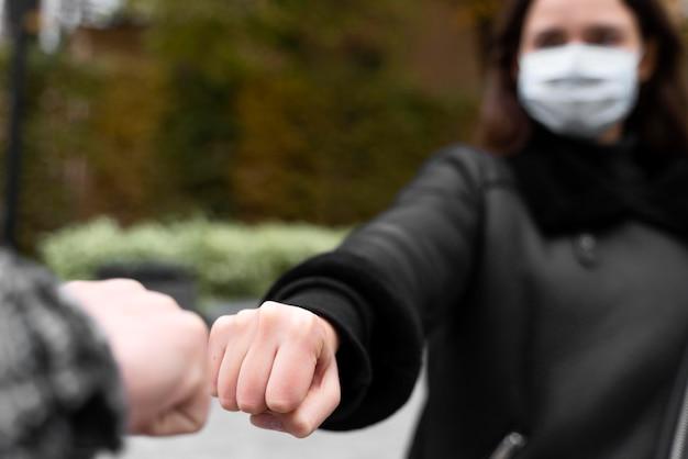 Альтернативные приветствия почти касались ударов кулаками размытой женщине Бесплатные Фотографии