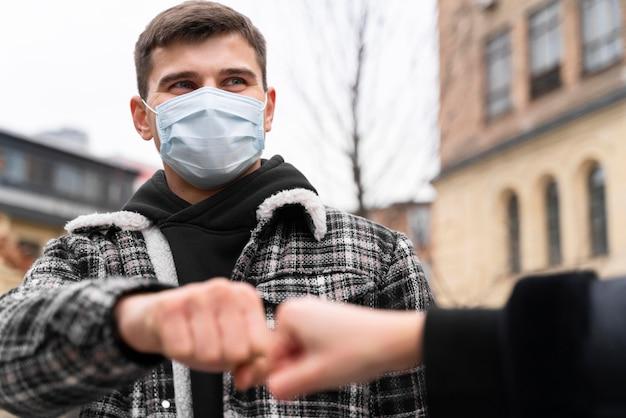 Saluti alternativi che quasi toccano il pugno urti l'uomo con la maschera Foto Gratuite