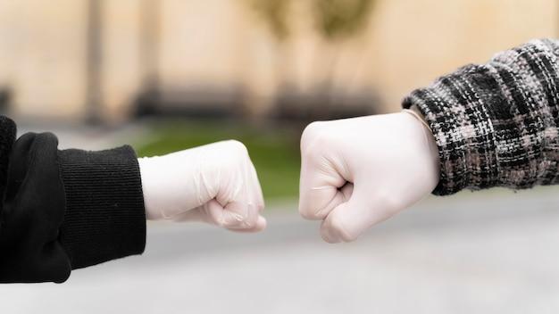 手袋で拳のバンプにほとんど触れる代替の挨拶 無料写真