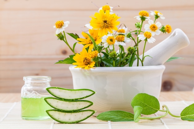 Alternative health care fresh herbs and mortar on wooden background. Premium Photo