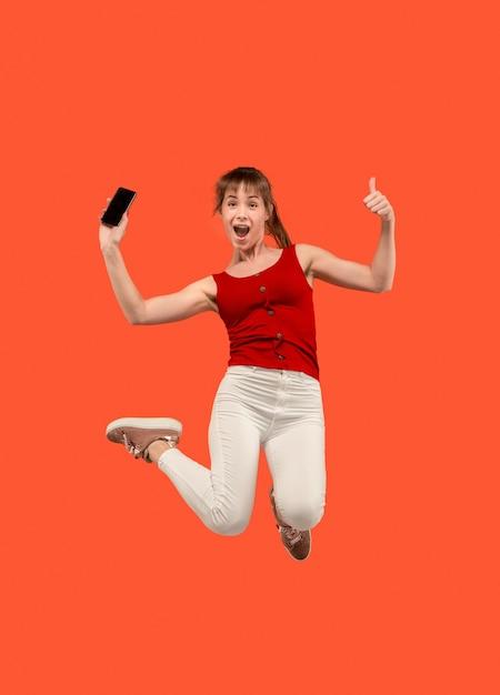항상 모바일. 빨간 스튜디오 배경 점프하는 동안 전화를 복용 꽤 젊은 여자의 전체 길이입니다. 모바일, 모션, 움직임, 비즈니스 개념 무료 사진