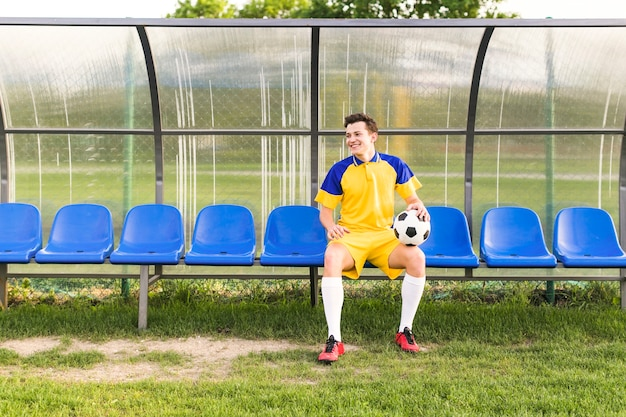 Amateur football concept with man on bench Free Photo