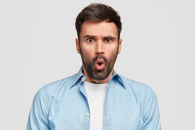 Изумленный изумленный бородатый парень недовольно смотрит, сердито хмурится Бесплатные Фотографии