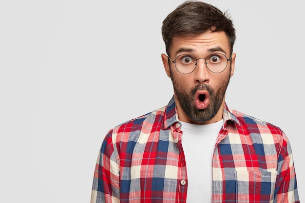 Amazed attractive unshaven man with opened mouth and bugged eyes, wonders latest news in college Free Photo