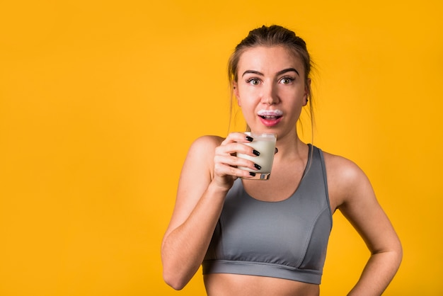 Amazed attractive young woman in sportswear with glass of milk Free Photo