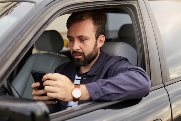 Uomo barbuto stupito in giacca blu e maglietta a righe, si siede al volante della macchina, tiene il telefono tra le mani e lo fissa sorpreso. Foto Gratuite