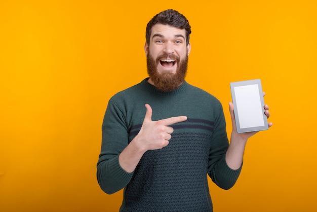 Изумленный бородатый человек, указывая на экран планшета Premium Фотографии