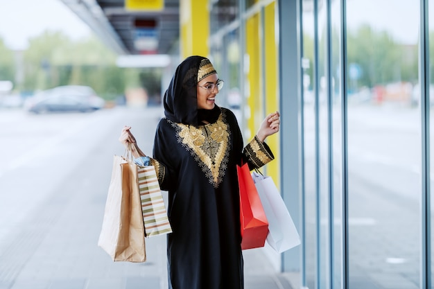 Amazed beautiful muslim woman in traditional wear standing outdoors with shopping bags in hands and looking at shop window. Premium Photo