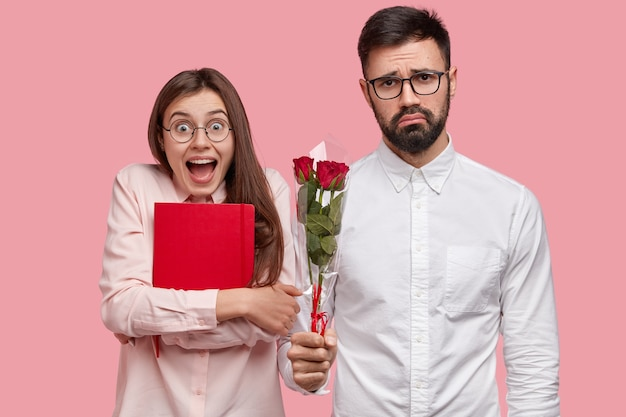驚いた美しい女性は、男性のウインクからプレゼントを受け取り、赤いメモ帳を持って、花を手に入れて幸せです。悲しい厄介な男はグループメイトとの最初のデートをし、バラをプレゼント 無料写真