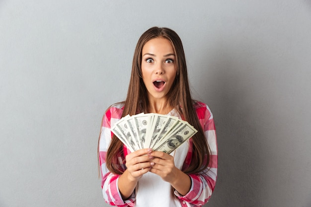 お金を保持している格子縞のシャツで美しい若いブルネットの女性を驚かせた 無料写真