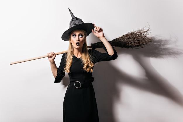 Пораженная блондинка-ведьма, касаясь своей волшебной шляпы. привлекательная девушка-вампир готовится к карнавалу в хэллоуин. Бесплатные Фотографии