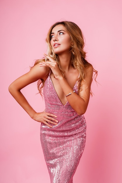 Изумленная белокурая женщина с представлять ветреных волос. розовая стена. великолепная модель. восторженные эмоции. Бесплатные Фотографии