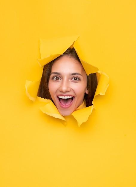 カメラに向かって明るく笑っている破れた黄色い紙のバナーの穴に現れる驚いたブルネット Premium写真