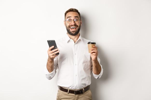커피를 마시고, 휴대 전화에서 멋진 온라인 제안에 반응하고, 서서 놀란 사업가 무료 사진
