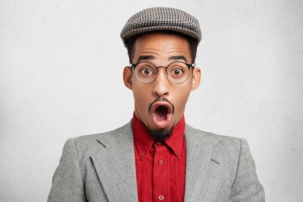 Stupito ragazzo hipster dalla pelle scura indossa berretto e giacca vecchio stile, apre la bocca in totale sorpresa, Foto Gratuite